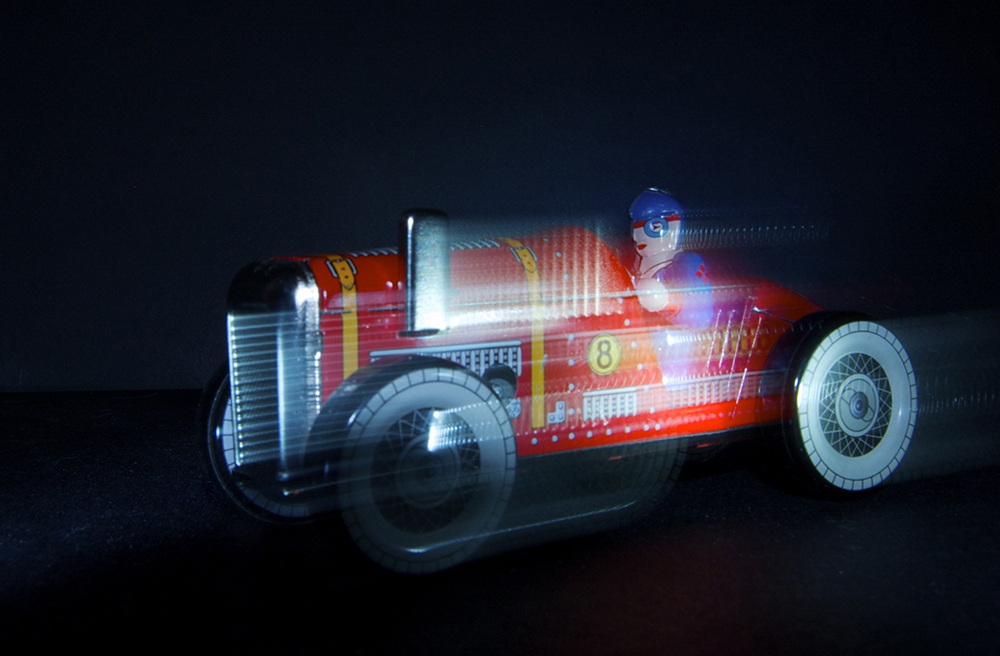 Toy red racing car in motion photographed by Beowulf Mayfield