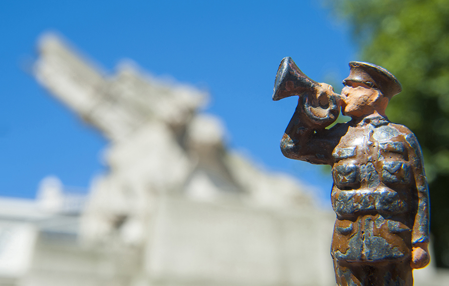 Lead toy soldier playing bugle with the Artillery Memorial, London, in the background