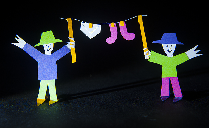 Photo of paper cut out figures holding up a washing line bearing pants and socks
